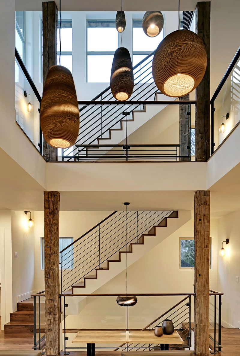 The four storey set of stairs is situated beside an atrium in the middle of this modern home long handmade pendant lights hang in the atrium filling the