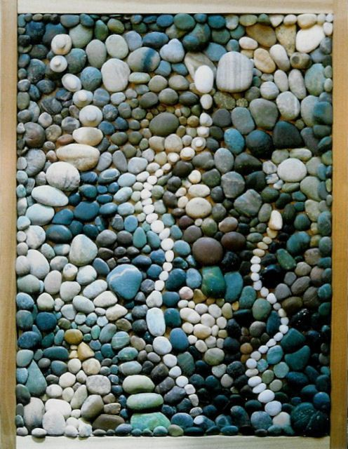 Pebble arrangement on coffee table with glass over top Can