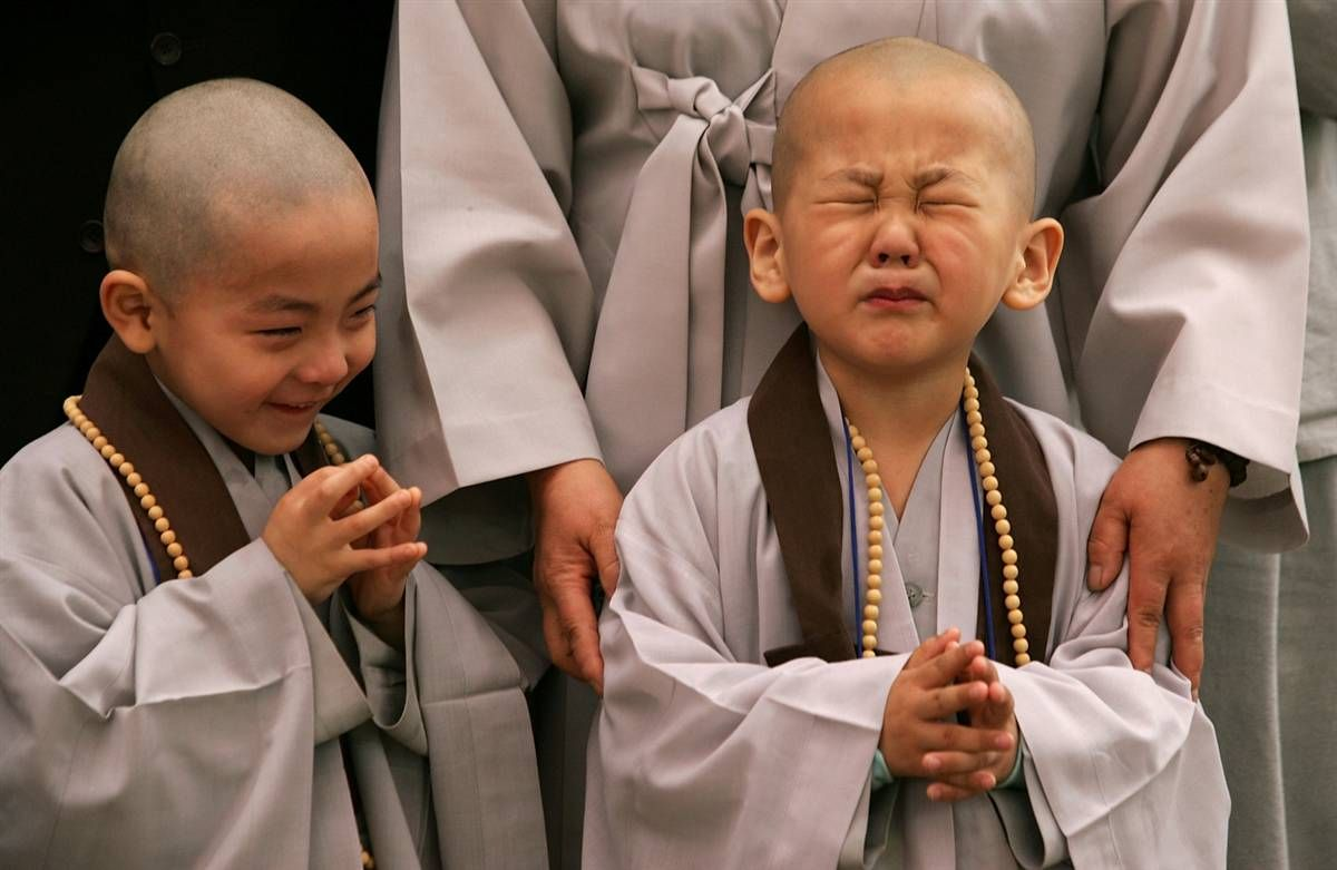 A child cries after having his head shaved by Buddhist