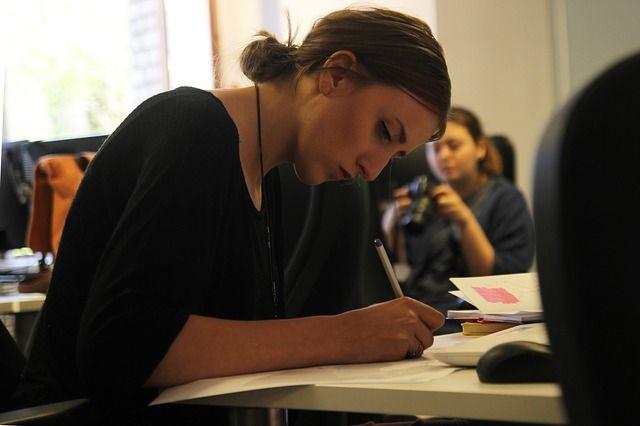 Foto de joven escribiendo en su escritorio