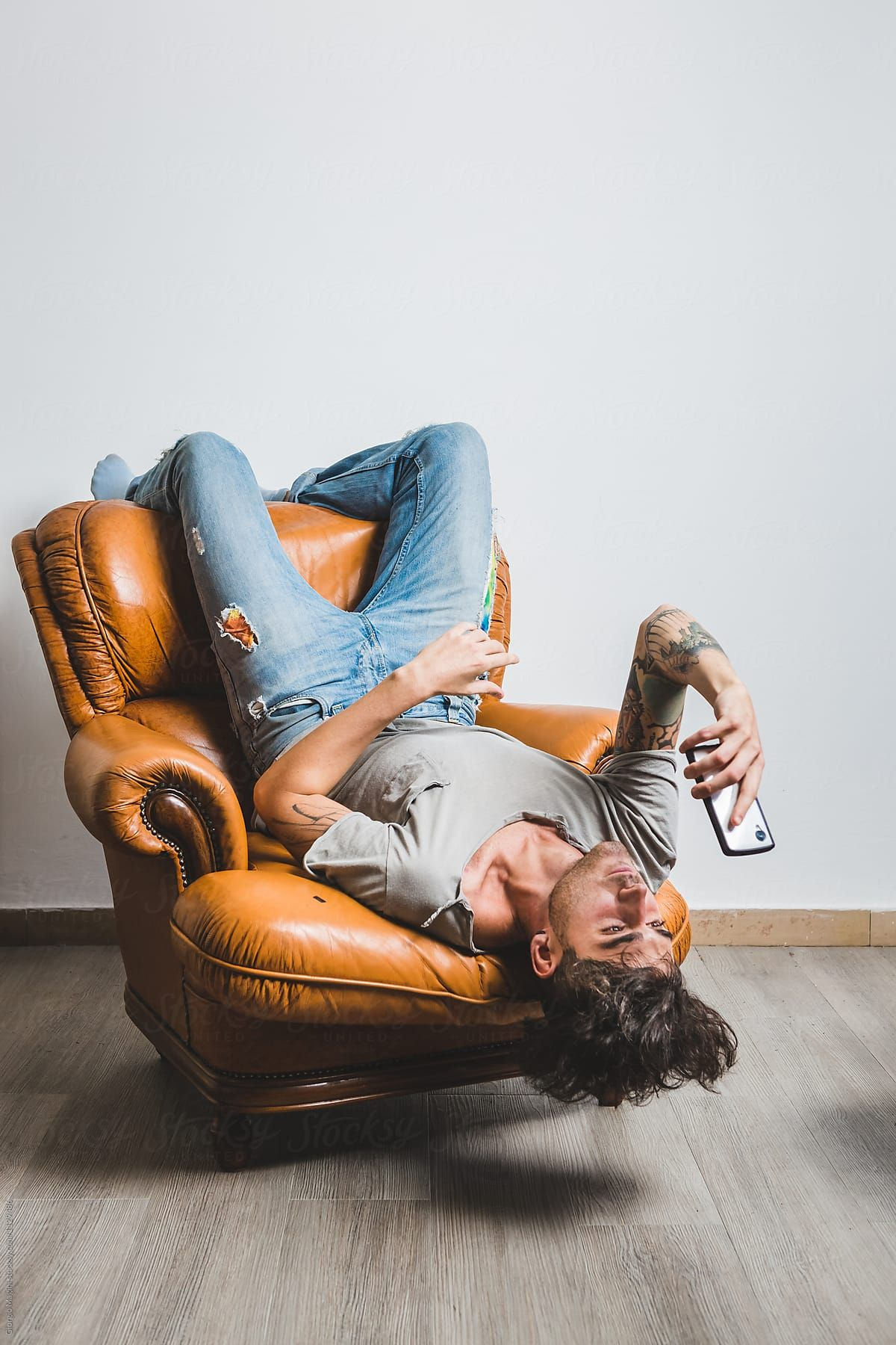 Upside Down Man Using Cellphone On A Leather Armchair By Giorgio Magini Technology Upside Do In 2020 Photography Poses For Men Model Poses Photography Sitting Poses