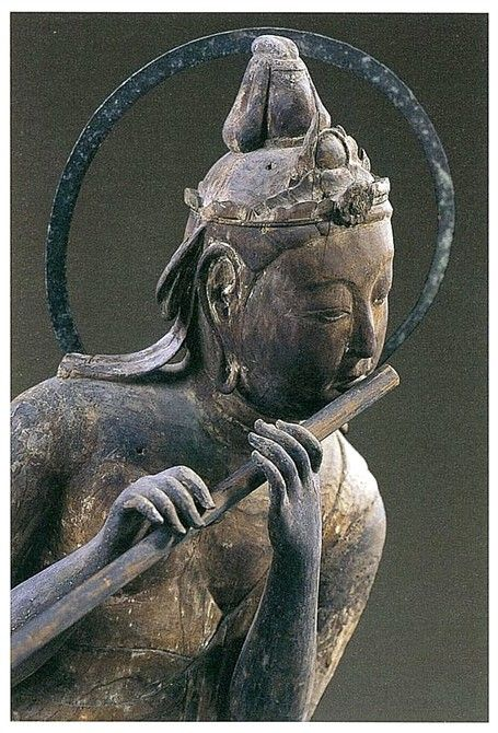 Bodhisattva on a cloud playing a Flute. 1053 AD carved wood. The Byodo-in Temple. Japan.