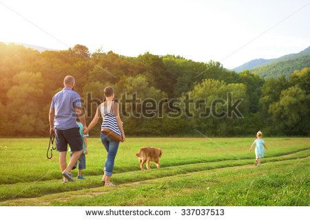 Beautiful young family with their pet dog, golden ...