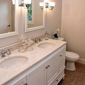 lovely bathroom with white double vanity paired with white marble countertops undermount sinks and polished chrome faucets