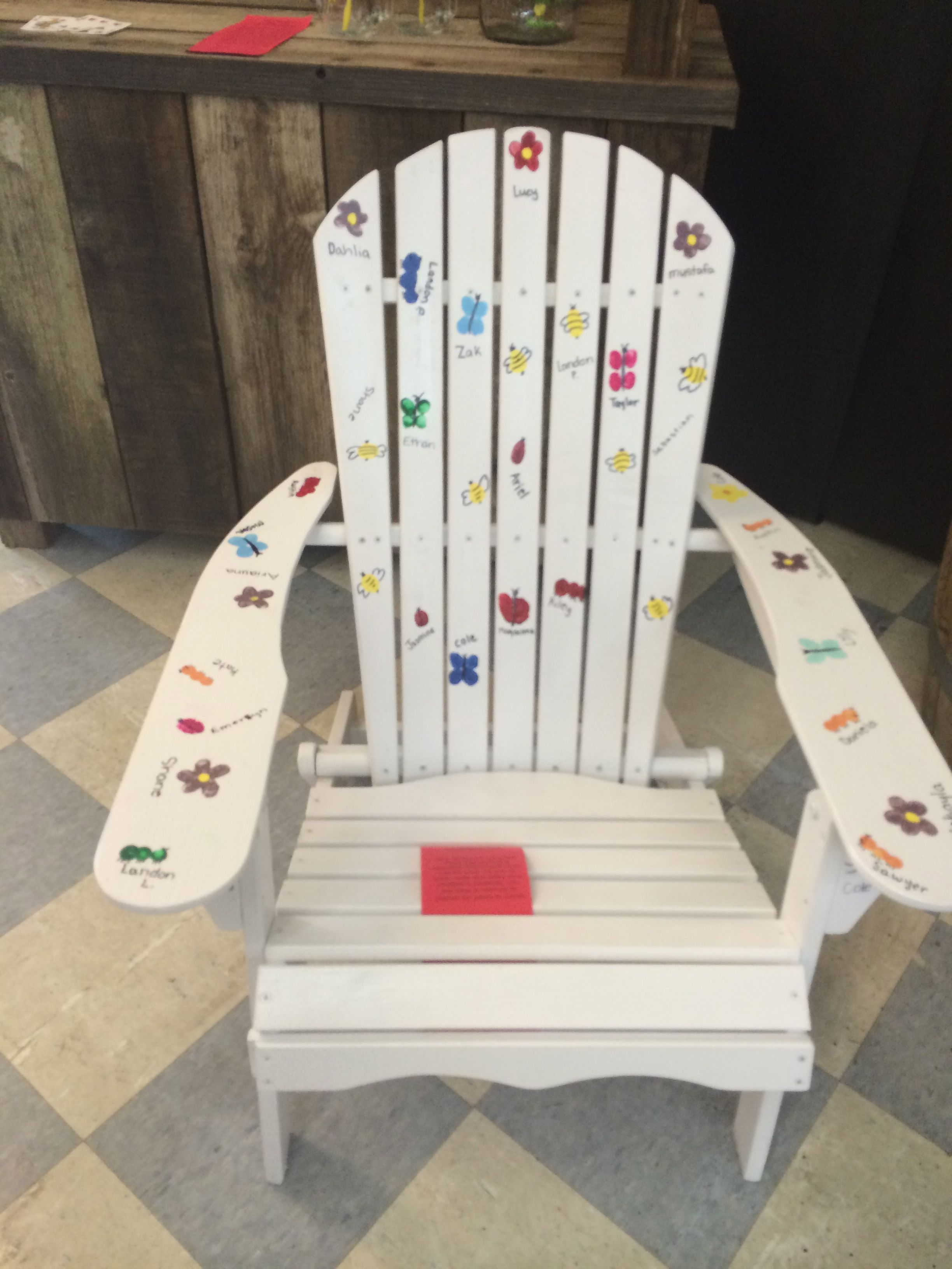 Adirondack chair with kids paintings of bugs all over it
