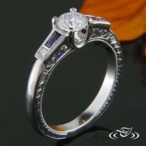 Custom 950 platinum engagement ring with .5ct round diamond center stone. Flush set tapered baguette with blue sapphires and diamonds in mounting shoulders. Side stones have milgrain edges with filigree panels and half wheat pattern on side faces.
