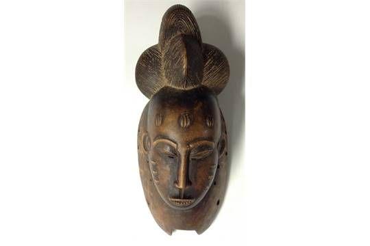 Tribal Art - a Baule mask, elaborated plaited coiffure, scarified cheeks, 38cm long, Ivory Coast