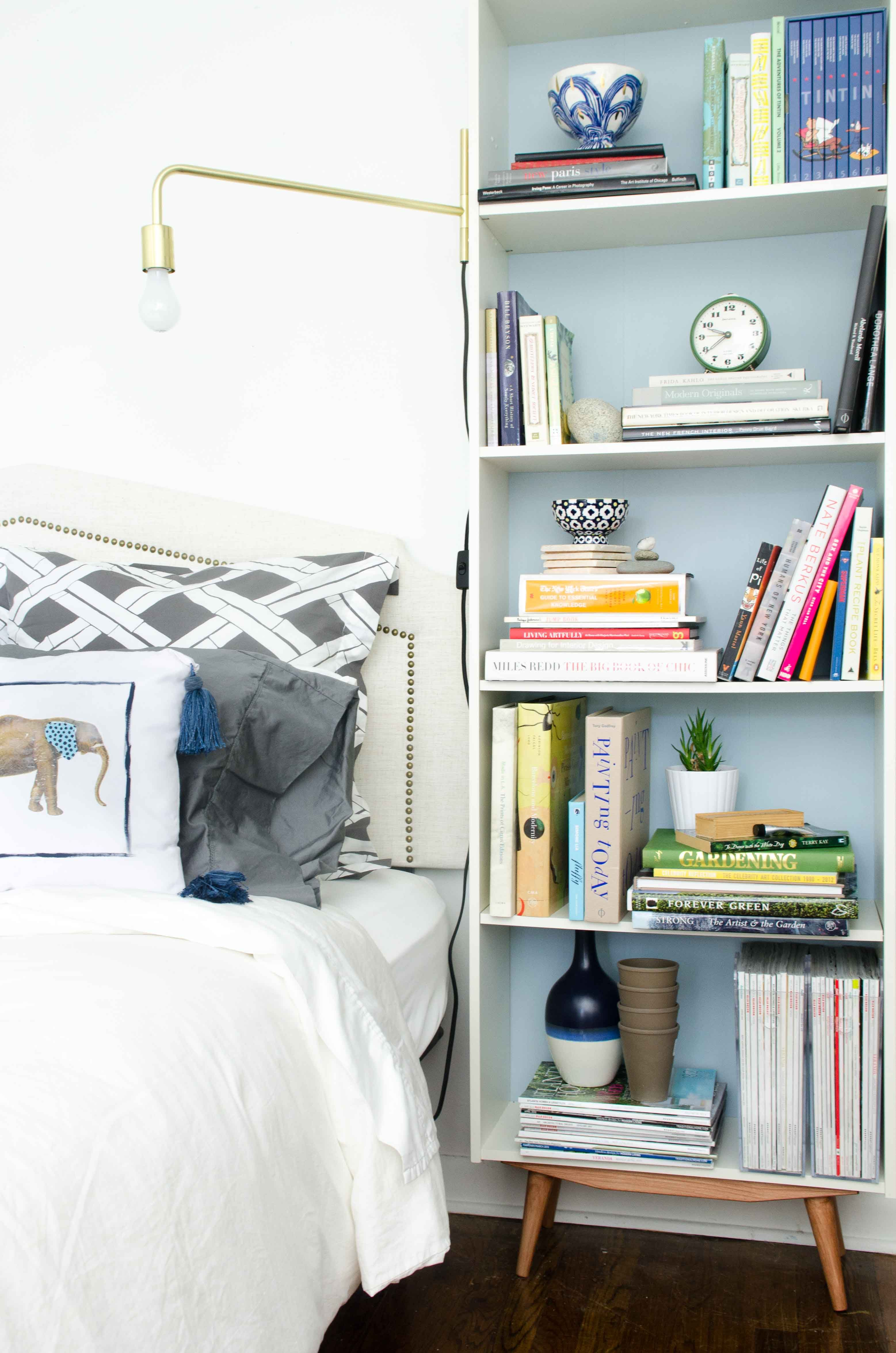 Diy mid century bookcase with brass swing arm sconce beside the bed via thouswellblog