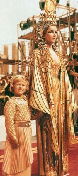 costumefilms: Cleopatra - Elizabeth Taylor wearing the most famous costume of the movie, a low-cut gold lamé dress with matching mantle and...