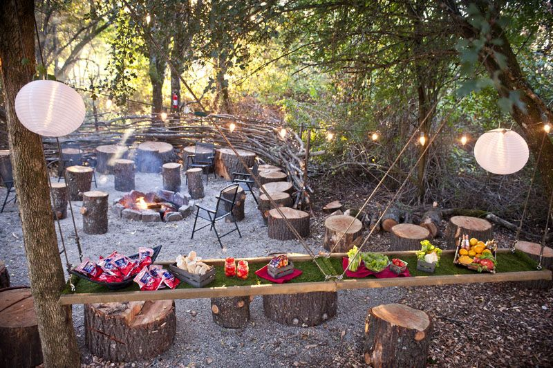 How gorgeous is this outdoor area for a rustic event? Love the twinkly lights and paper lanterns! And the tree stump seating is perfect for the theme | The Aerie at Eagle Landing | BravoEvent.com