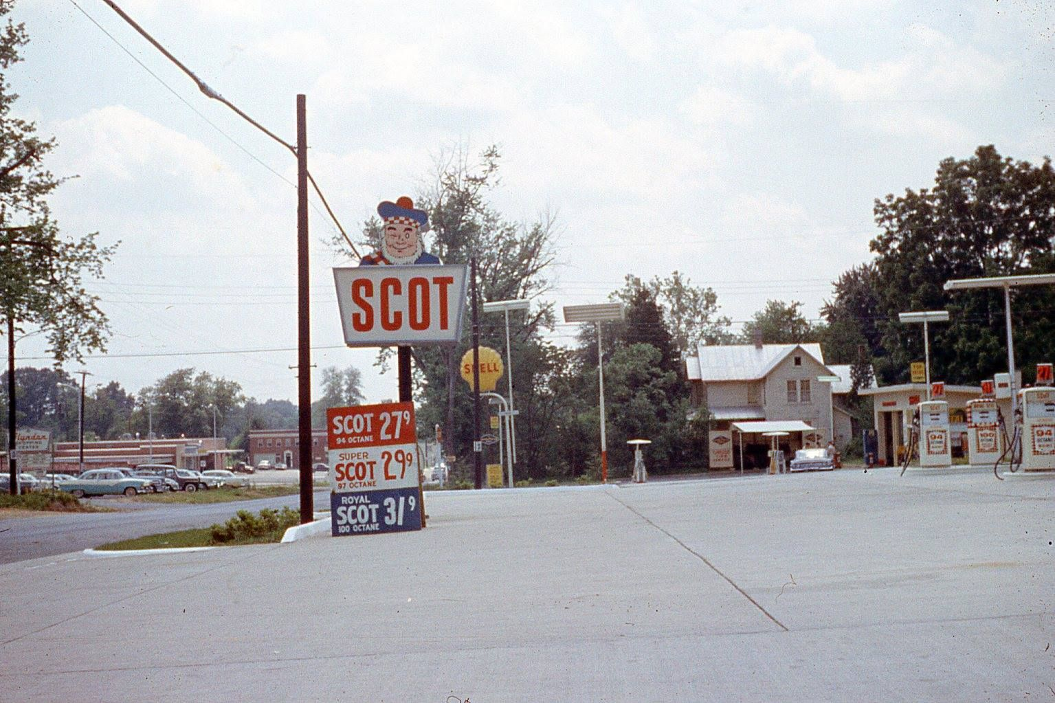 Scot gas station on Maple Avenue. Date unknown, but blue and white car in the lot is a 1956 Ford. Building behind the cars was then Southern States; the building across Park Street is now the Michel Rene building.