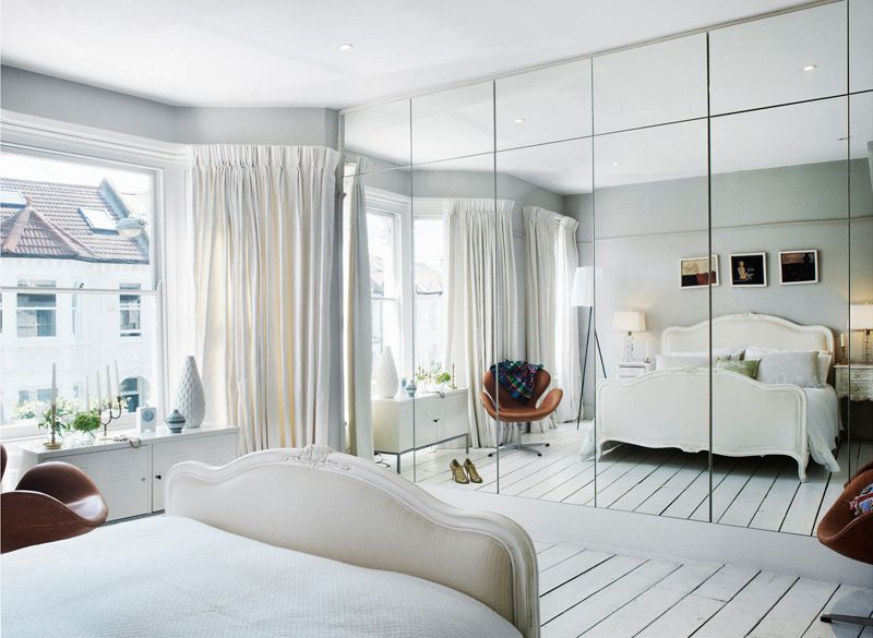 Wall of mirrored closets, wardrobes, storage. Reflects the light in a dark room and makes the room look bigger. Light and white small bedroom. Maximized storage floor to ceiling.
