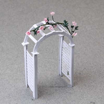 An arched garden arbor in 1:48 miniature scale made from a printable and card.