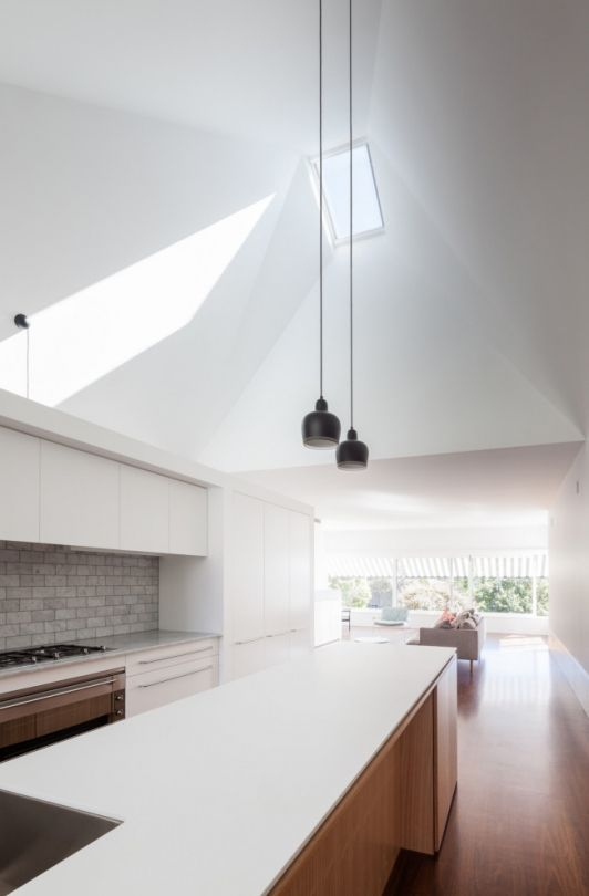 Kitchen extra high ceiling with skylight two small black pendant lights over island bench marble subway tile splashback marble and white benchtops ... & A 1920s bungalow becomes a cheerful beachside home in Sydneyu0027s ...