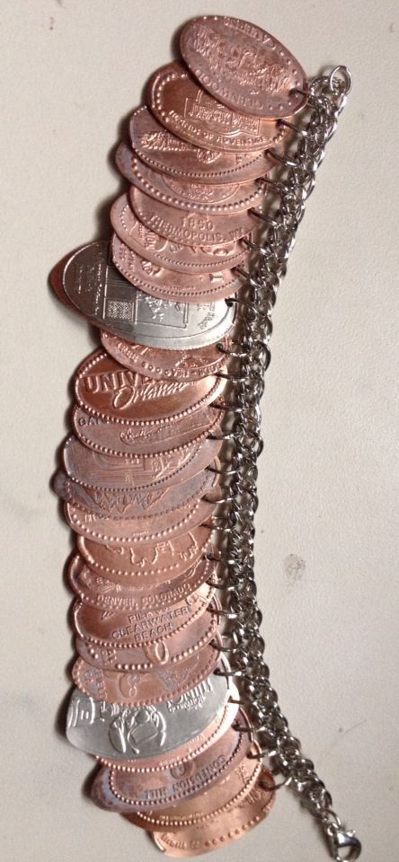Souvenir penny charm bracelet. I have been collecting smashed pennies from all over the world for years! I finally decided to drill a small hole in each one, and use a jump ring to attach them all to a chained bracelet. This is the final result; my very own souvenir bracelet of memories! #disney #craft #disneycraft #diy #disneycrafts