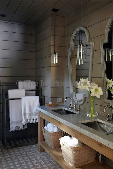A double marble-topped washstand in the bathroom houses a pair of stainless steel basins complemented with a pair of mirrors on the wood-cla...