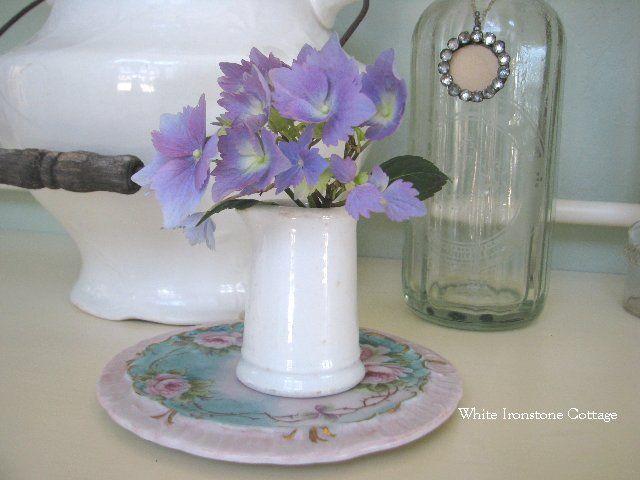 A Small white ironstone pot with a tiny  hydrangea sprig