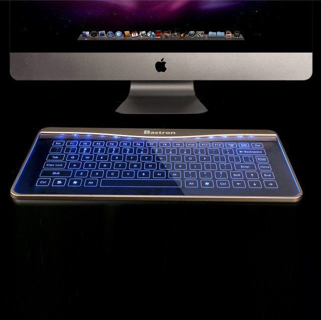 Glass Keyboard by Bastron. Available with a pink backlight or a blue backlight. It's not only a glass keyboard, but it is also a mouse that has touch sensitive key controls and gestue controls. Plug and play Micro USB to connect your computer or other devices. Supporst Windows/Android/ IOS. Made of aluminum and tempered glass. Please allow 4 weeks for US delivery/ 4-6 weeks for international delivery.