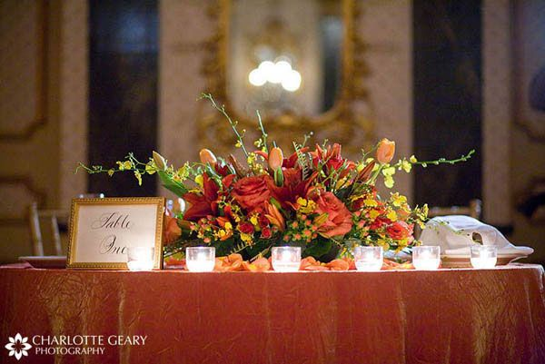 Wedding sweetheart table with orange red and yellow for Orange centerpieces for tables