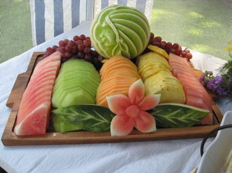 Seasonal Fruit Platter Arrangement with Fruit Sculpture and Garnish. Calbert Culinary Arts. Watermelon sculpted into Hawaiian flower. Melon carved with Native American man
