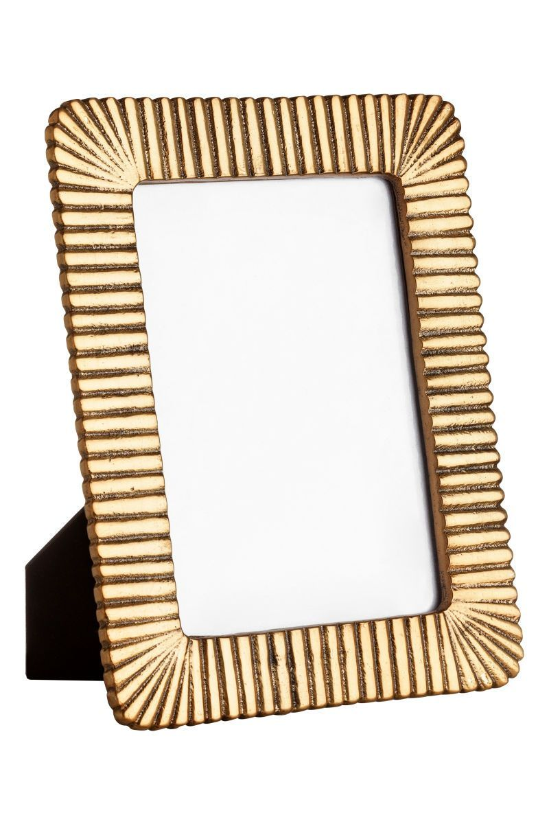Gold-colored. Photo frame in fluted metal with a stand at back. Fits ...