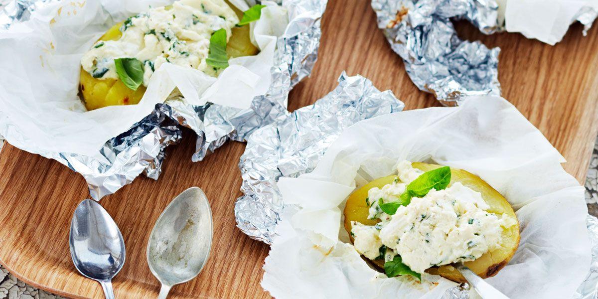 Pese ja halkaise perunat kuorineen. Sipaise leikuupinnoille öljyä ja mausta kevyesti suolalla. Kääri perunapuolikkaat folioon ja nosta ne grilliin keskilämmölle. Grillaa 45 - 60 minuuttia. Hienonna vuohenjuusto haarukalla ja sekoita juuston joukkoon muut täytteen ainekset. Avaa foliot kypsien perunoiden ympäriltä ja lusikoi perunoille täytettä. Tarjoile heti.