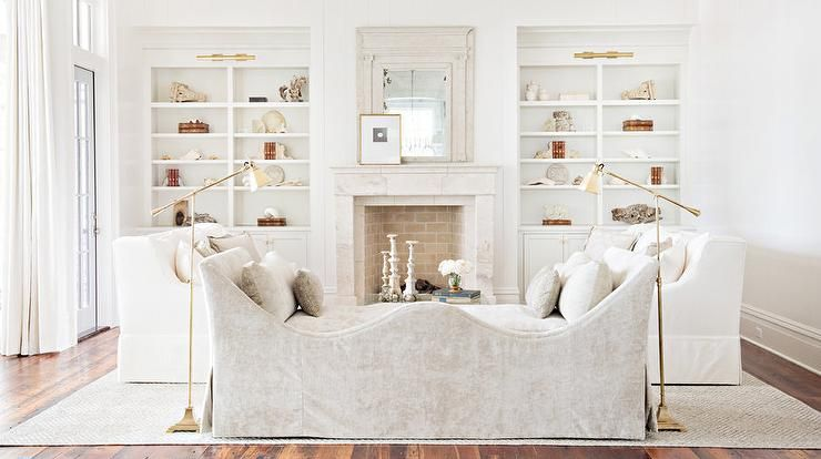 Lit by two antique brass pharmacy floor lamps, a gray curved chaise lounge faces two white skirted sofas sat on a light gray area rug while this cottage living room's window's are dressed in long white curtains.