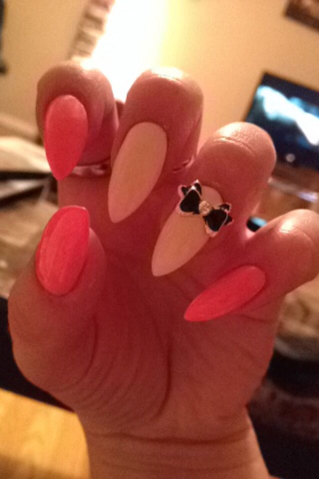 pink and cream colored pointed acrylic nails with black