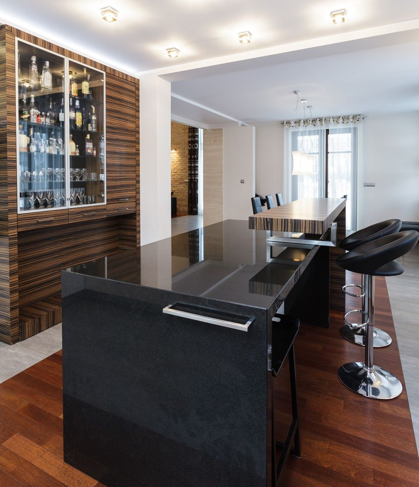 Bar Area Inside Home With Black Quartz Countertops And Black Leather And  Chrome Barstools