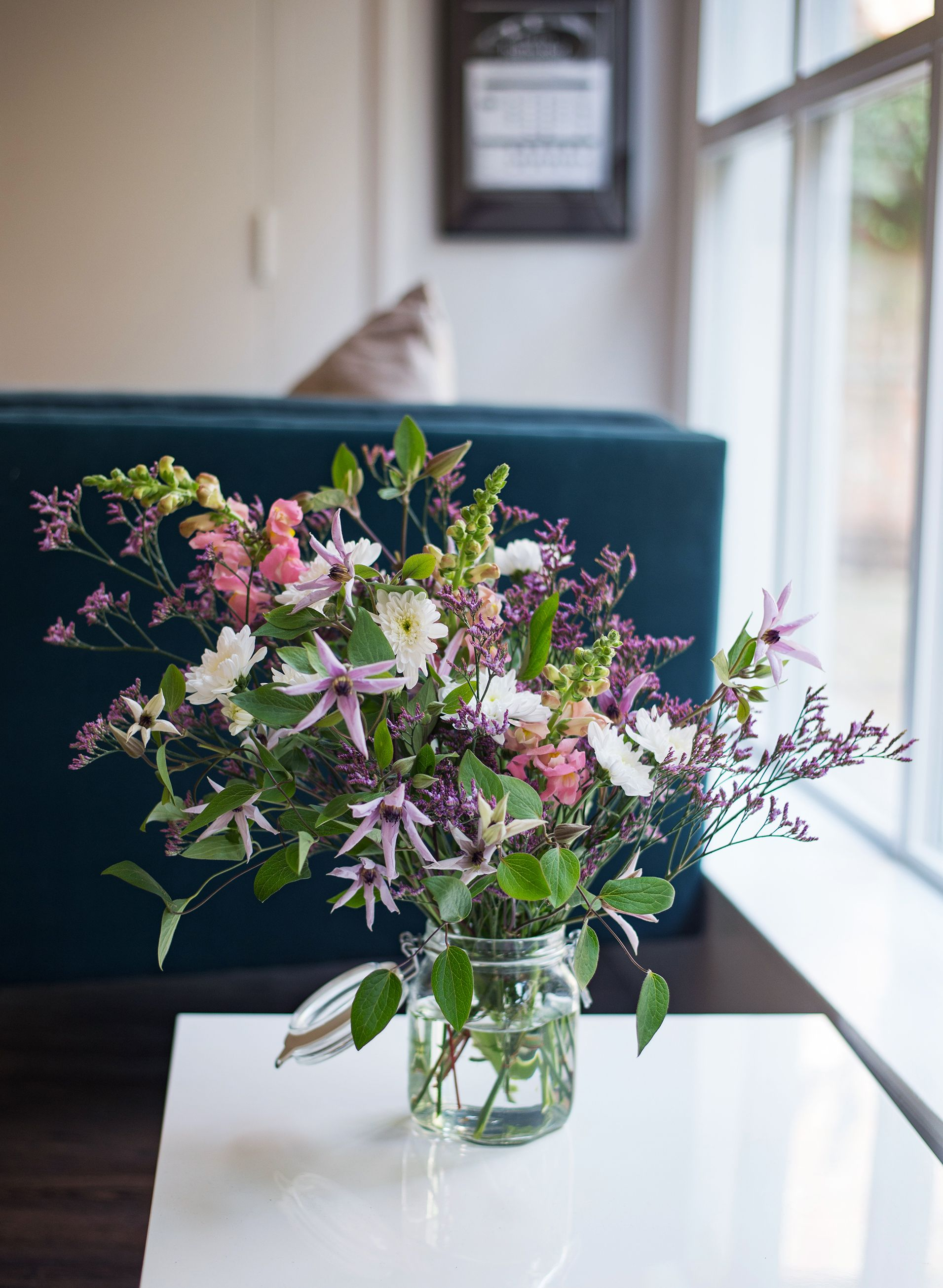 Starry clematis flowers and snapdragons mixed with purple limonium
