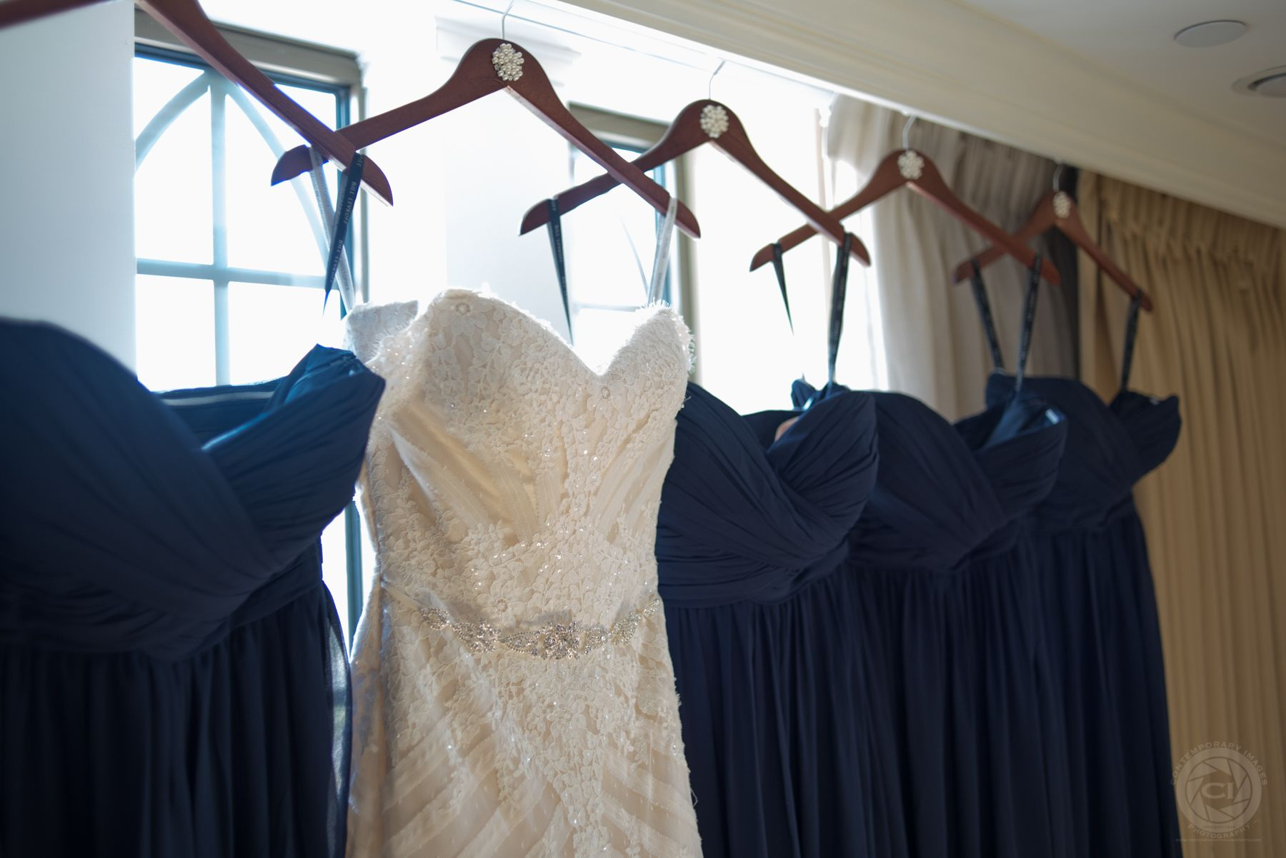 Navy blue chiffon bridesmaid dresses hanging next to wedding gown Loved the matching hangers for the bride and bridesmaids