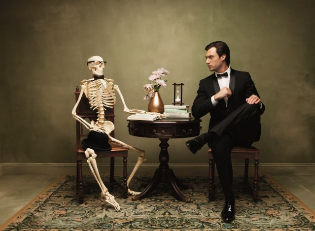 Man Sitting Next To A Skeleton At A Table