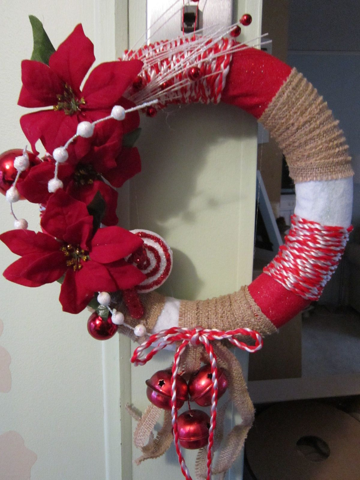 ...at the Cottage - small wrapped foam wreath using red & white felt, burlap and red & white cord with poinsettias and bells created by DonElla Nielsen