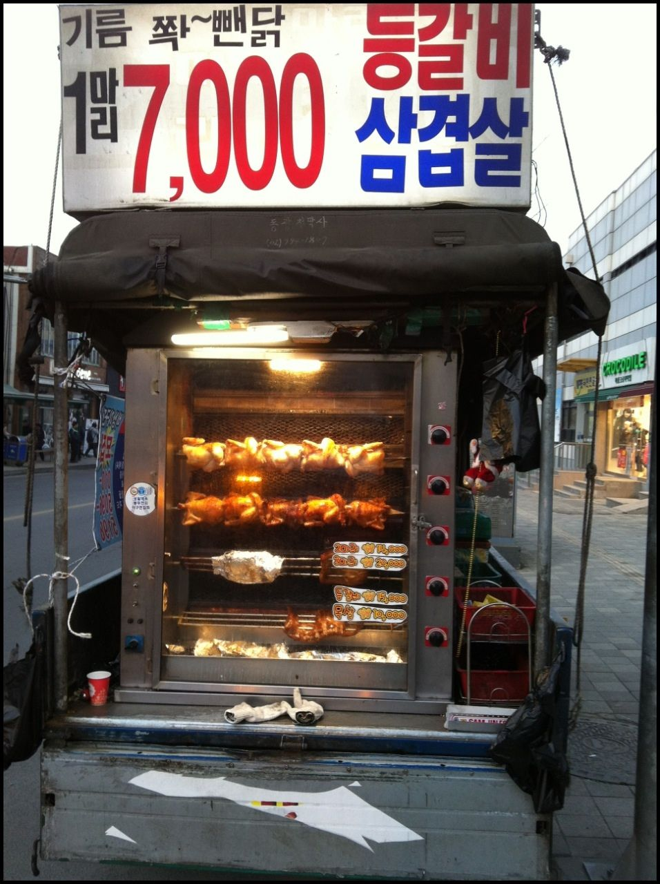 Rotisserie chicken trucks on the side of the street in