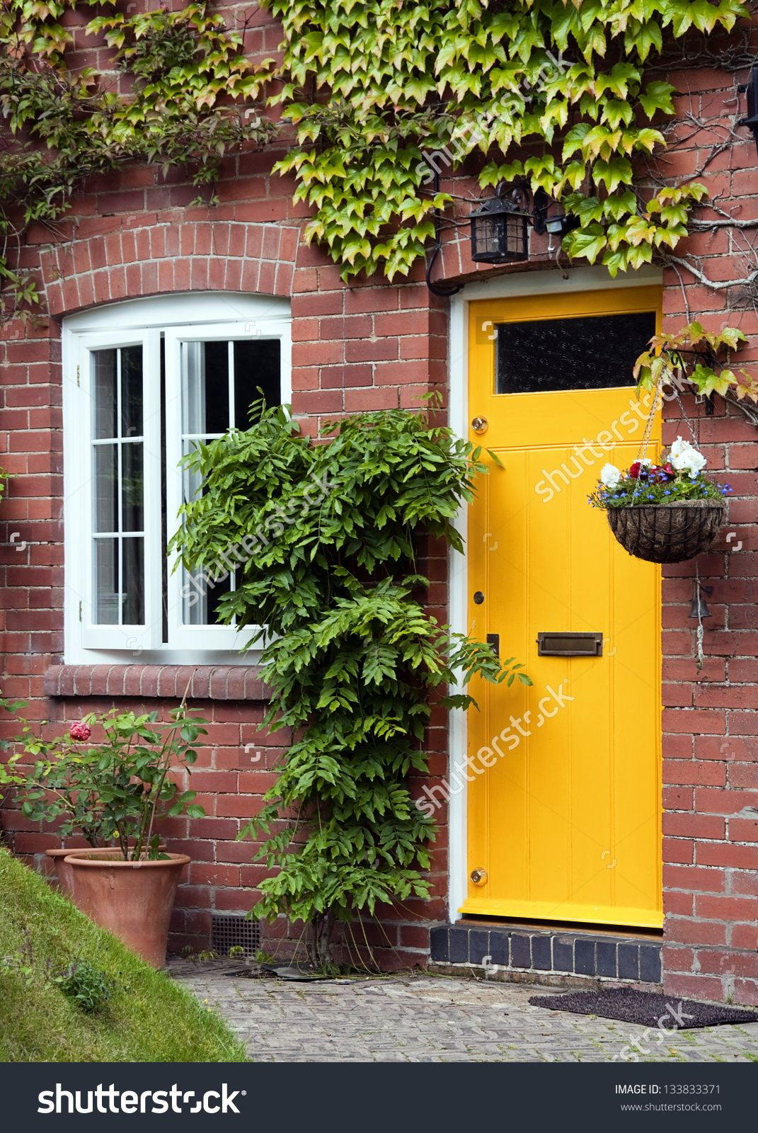 Yellow Front Door Entrance And Old Style Window Of A Red Brick
