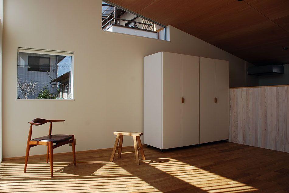 リビングダイニング 勾配天井によって南側は最大で3 5m程の天井高さ 西側壁にはシャープな枠廻りの窓が2つあり 見える景色が際立っている 左側の窓は 片引き窓になるよう納まりを工夫をしている 棲家 住宅 平屋住宅