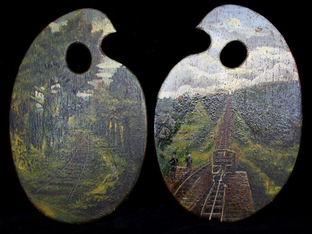 "Pair of miniature painted artist's palettes with railroad themes. One palette shows a railroad track in the woods and the other a cog railway. Oil on wood, unsigned. Each palette measures 7.75"" x 4.5""."