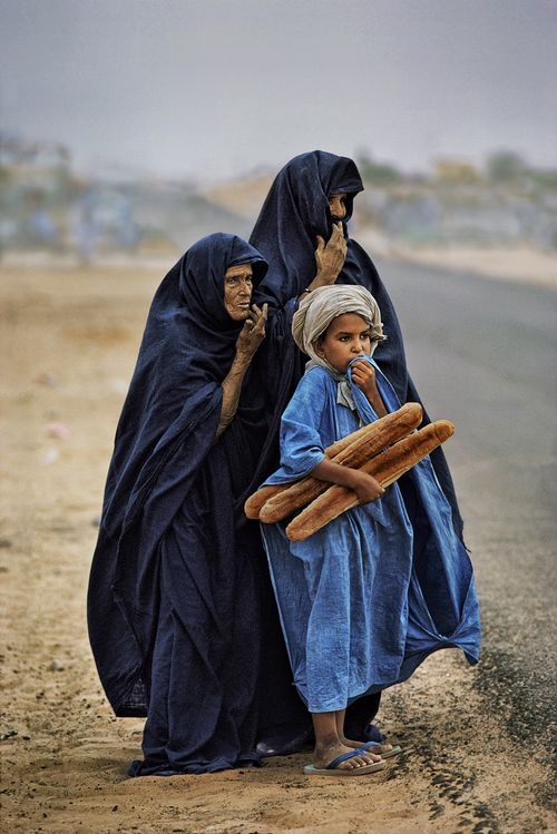 stevemccurrystudios:  A boy with his mother and grandmother hold the day's bread, Tiguent, Mauritania. The vivid blue stands out in vivid re...
