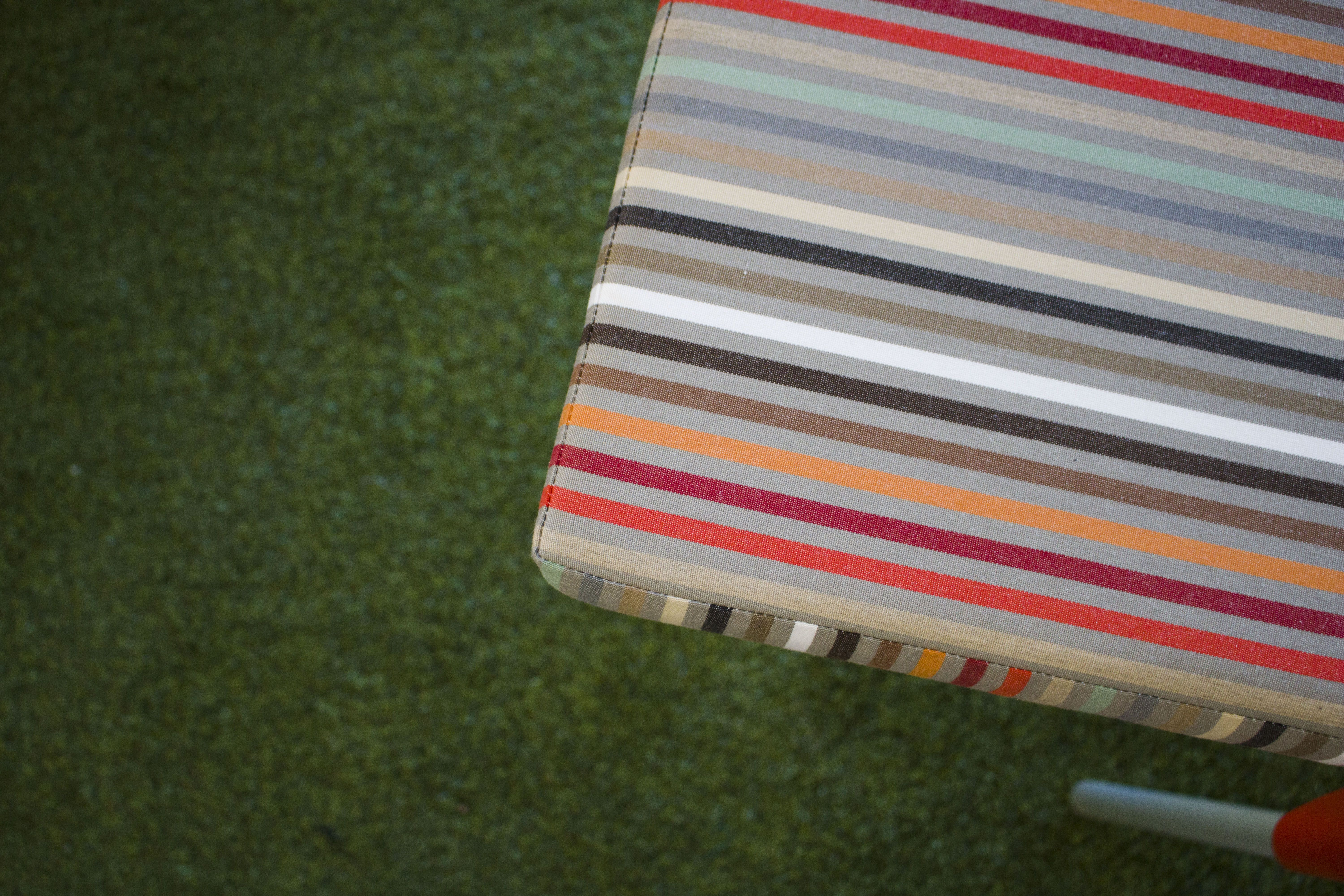 Colorful striped chair cushion with a neutral base color