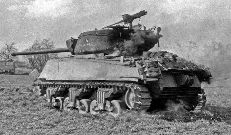 "A totally destroyed & burning Sherman tank. There was a reason troops early on called them ""match-boxes""...."