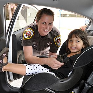 Sheriff's deputy adjusts straps on 's safety seat   Alexandria ...