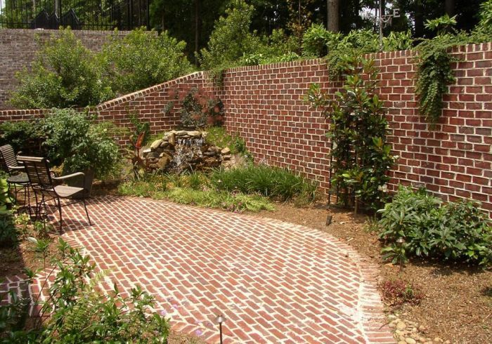 Brick patio and retaining wall with small pondless water feature.