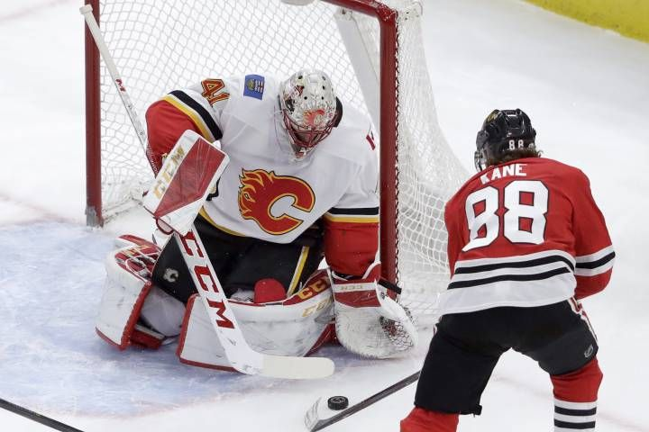 Calgary Flames goaltender Mike Smith makes a save on a shot by Chicago Blackhawks' Patrick Kane during the second period of an NHL hockey game Tuesday, Feb. 6, 2018, in Chicago. (AP Photo/Charles Rex Arbogast)