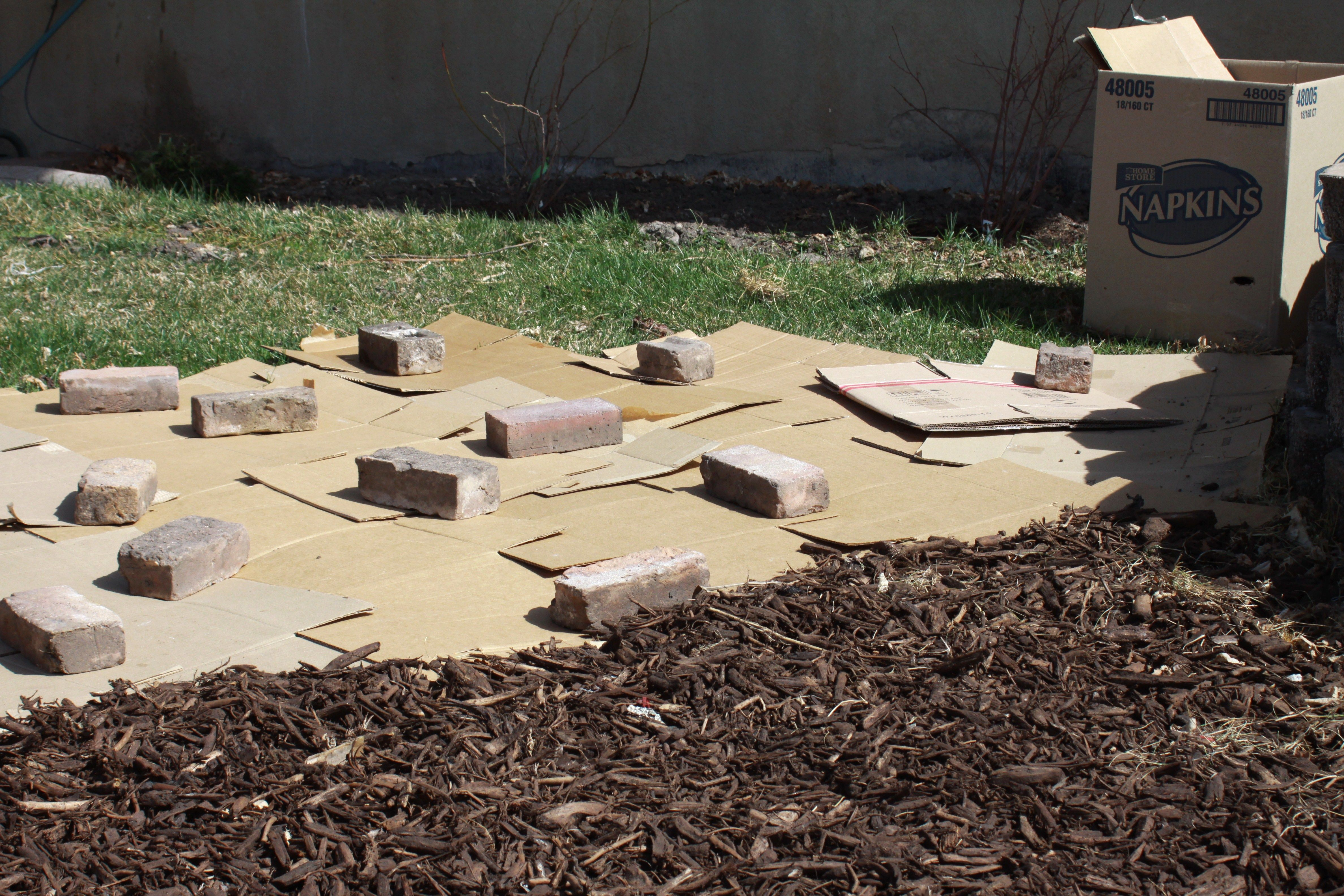 Lay interlocked cardboard boxes on your grass and spread mulch over the top. Wet it down to compact the layers and say goodbye to your grass. (Works much better than newspaper!)