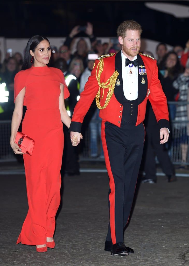 Meghan Markle Color-Coordinates With Prince Harry in a Red Safiyaa Cape Dress