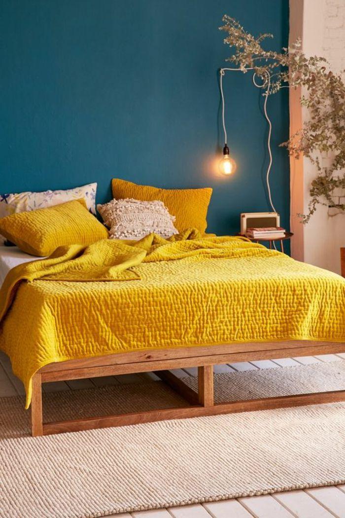 dco chambre adulte lit en bois avec couverture et coussins en jaune rayonnant avec peinture chambre adulte en bleu marine sur un mur