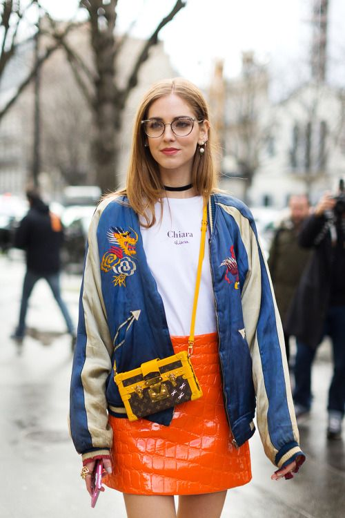promo code 805f7 843b1 Chiara Ferragni street style outfit wearing cat-eye glasses, choker  necklace, graphic T-shirt, bomber jacket, patent leather skirt, and mini  bag.