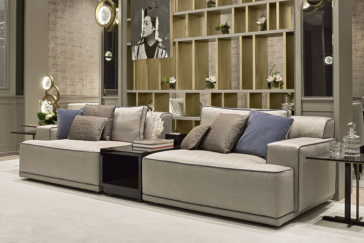 This living area offers an elegant and understated atmosphere thanks to the Dahlia sofas in fabric with contrast piping and the Magritte bookcase displaying a warm bronze finish
