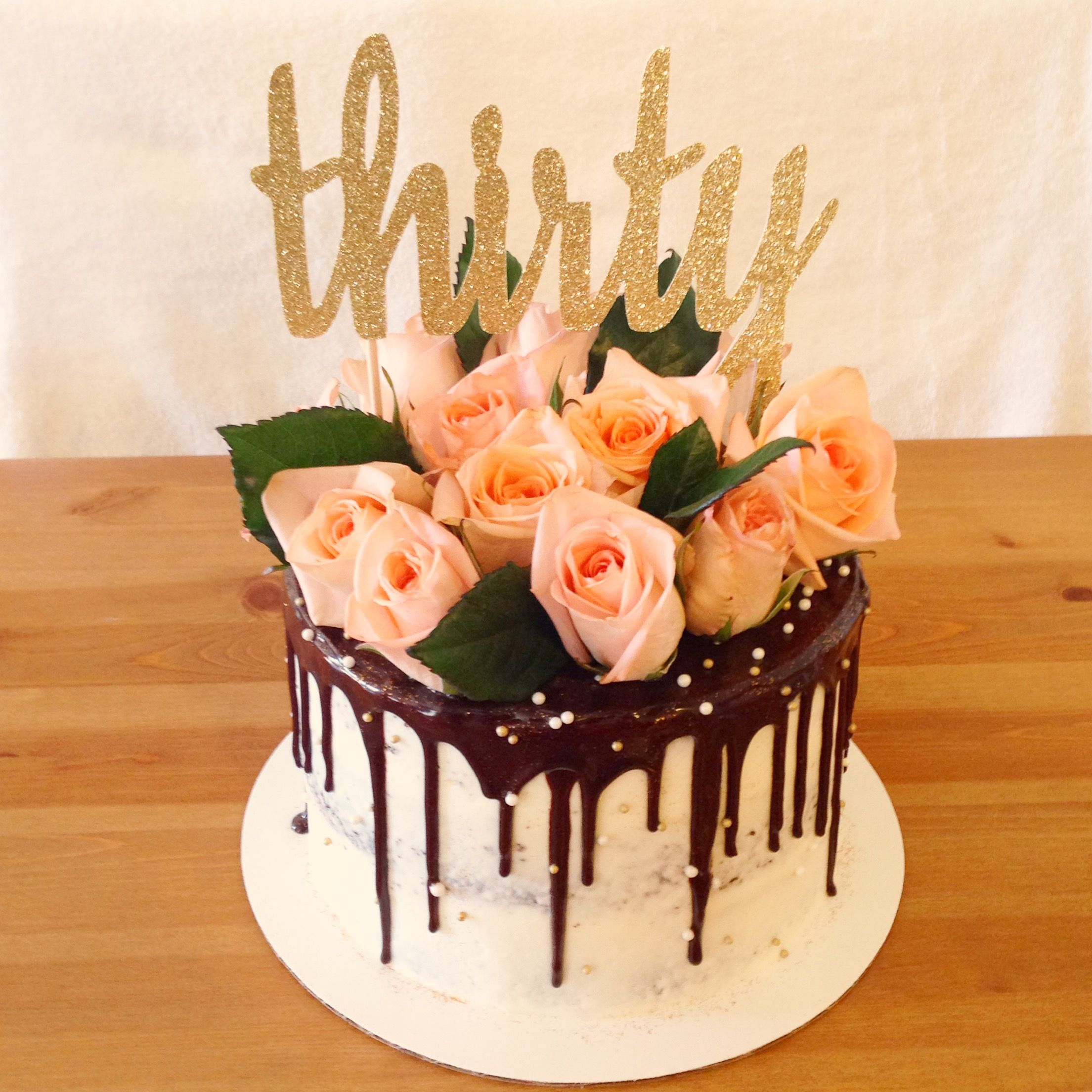 Chocolate drip cake topped with fresh roses for a thirtieth birthday ...