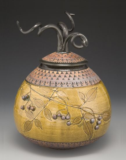 """""""Egg Medusa Jar with Berries"""" Created by Suzanne Crane Flora from the Blue Ridge Mountains imprints this wheel-thrown stoneware lidded jar with twined final. Glazed in amber celadon, with black trim and red iron oxide on the hand-stamped border. Leaf specimens vary seasonally. Each twisted handle is unique and will vary from image shown."""
